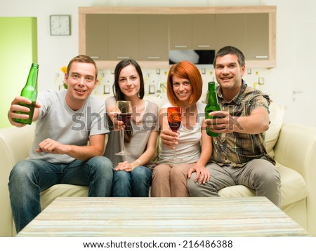friends sitting at home on sofa, making a toast with drinks and watching tv