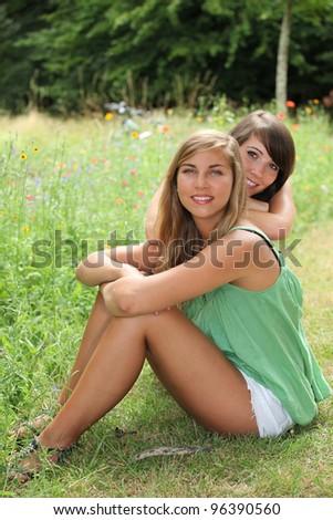 Friends sitting in a field - stock photo