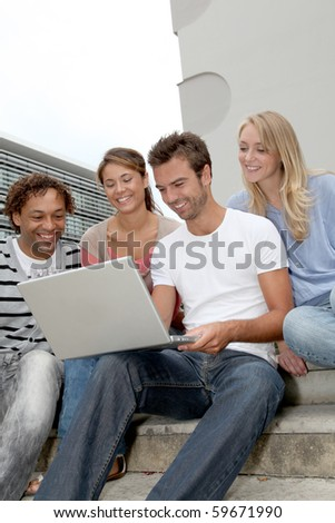 Friends sitting in stairs with laptop computer