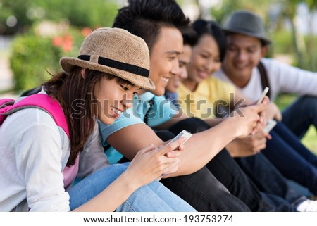Friends sitting in the park and using their smartphones - stock photo