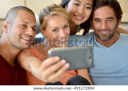 Friends sitting on couch taking selfie picture