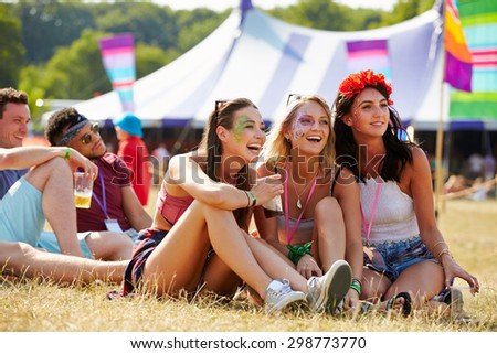 Friends sitting on grass  watching a gig at a music festival - stock photo