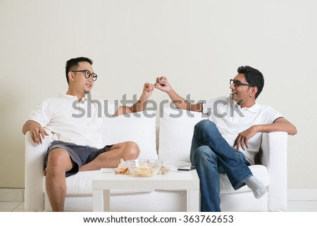Friends sitting on sofa and giving hand promise at home. Multiracial people friendship.