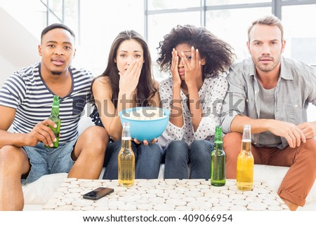 Friends sitting on sofa and having beer and popcorn in living room - stock photo