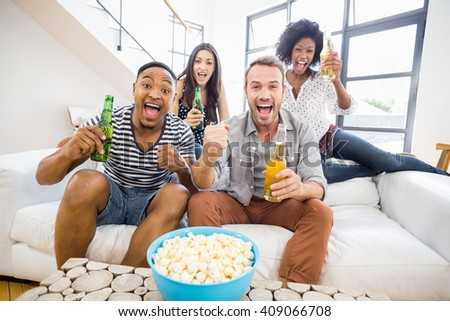 Friends sitting on sofa and holding beer bottles in living room - stock photo