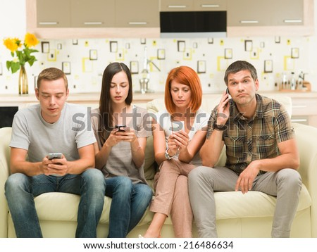 friends sitting on sofa and playing on their phones - stock photo