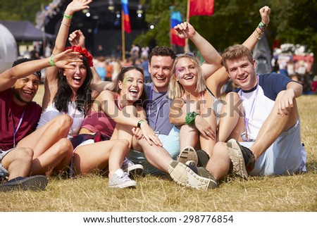 Friends sitting on the grass cheering at a music festival - stock photo
