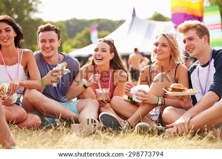 Friends sitting on the grass eating at a music festival - stock photo
