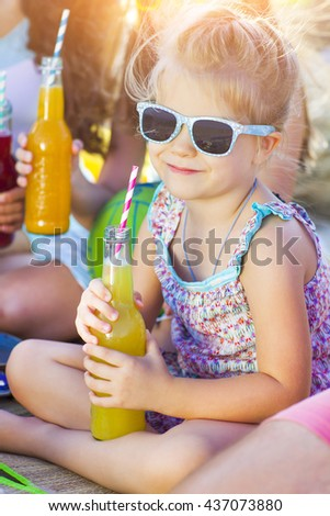 Friends sitting on the sand at the beach at the summer picnic. Little smiling girl with lemonade
