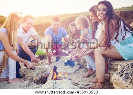 Friends sitting on the sand at the beach in circle with marshmallow on the beach
