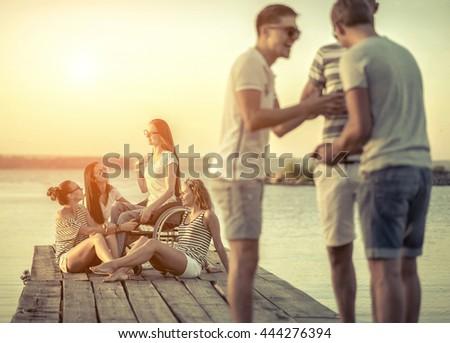 Friends sitting on wooden pier under sunset light. - stock photo