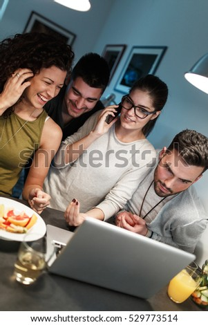 Friends sitting together in living room and watching movie on on laptop