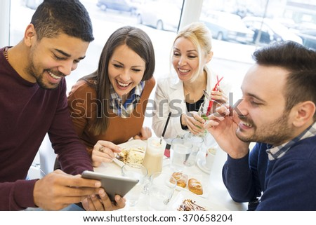 Friends smiling and sitting in a cafe, drinking coffee and enjoying together - stock photo