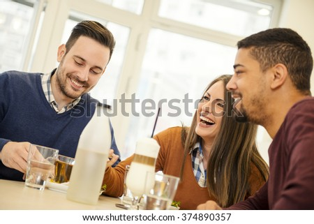Friends smiling and sitting in a cafe,drinking coffee and enjoying together