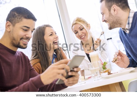 Friends smiling and sitting in a cafe, eating cake and enjoying together. - stock photo