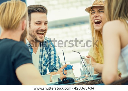 Friends smiling and sitting in a coffee shop, drinking coffee and enjoying together - stock photo