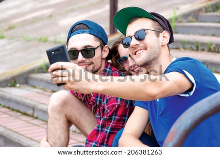 Friends smiling at the camera. Young friends have fun together on the street and smile at each other. Funny guys make Selfie