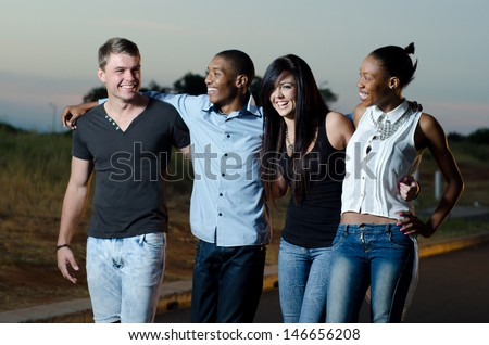 friends smiling while holding each other at sunset - stock photo