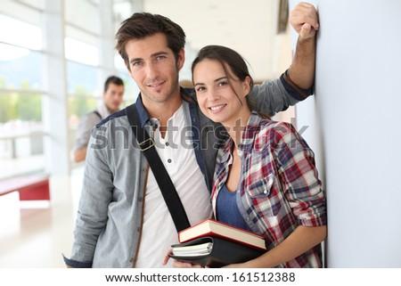 Friends standing in university hallway  - stock photo