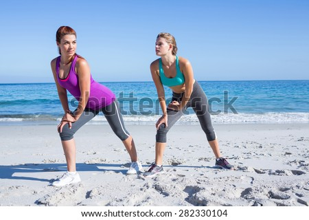 Friends stretching together beside the water at the beach