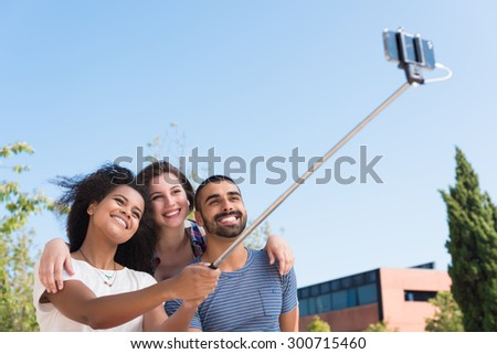 Friends taking a photo with a selfie stick - stock photo