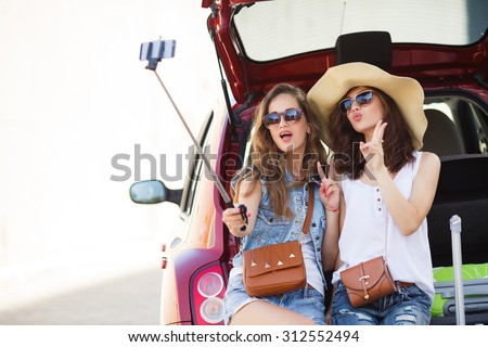 friends taking a selfie in the back of the car before leaving for vacations. Two women taking self portraits sitting in back car with suitcases. Vacation, trip concept. Road travel. - stock photo