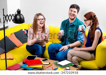 Friends talking and laughing with coffee cups on the yellow couch - stock photo