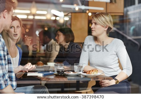 Friends talking on a coffee break at busy cafe - stock photo