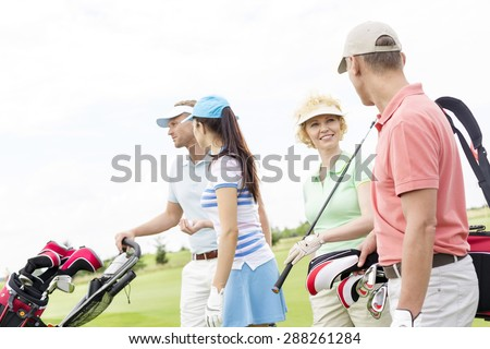 Friends talking while walking at golf course against clear sky - stock photo