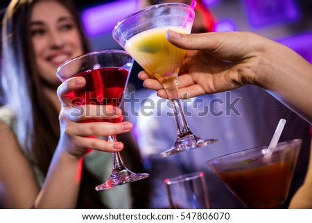 Friends toasting cocktail at bar counter in bar
