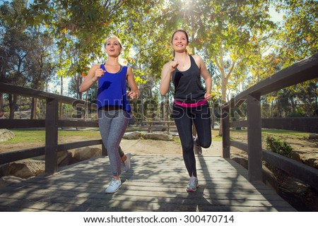 friends train and run jogging together to lose weight cardio training fitness in trees park - stock photo
