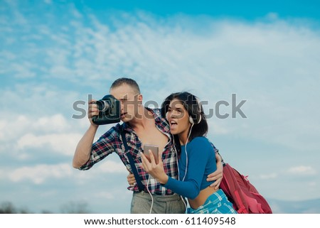 Friends Travel Backpacker Adventure Concept. Positive man and woman tourists taking camera in hands and photographing in city. Happy tourist couple traveling on holidays in Europe smiling happy.