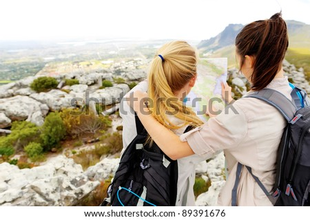 friends try to find their bearings on a map while hiking outdoors. leading a healthy lifestyle - stock photo