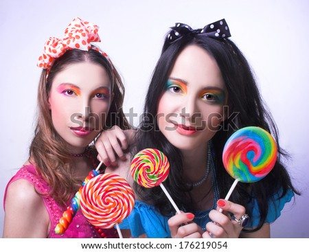 Friends. Two girls with creative visage and in bright cloth