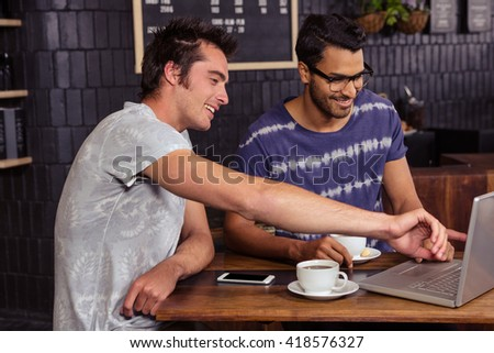 Friends using a laptop in a coffee shop
