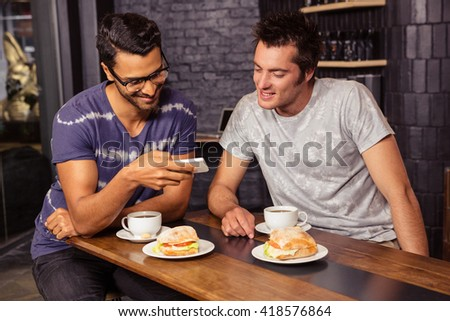 Friends using a smartphone in a coffee shop - stock photo