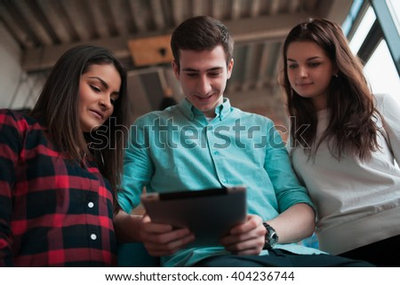 Friends using a tablet computer in the room
