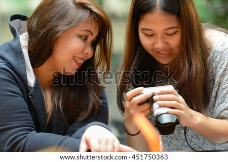 Friends using camera outdoors