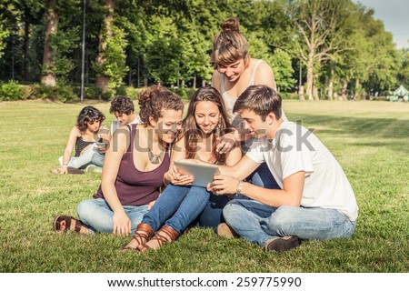 Friends using mobile devices in the park - stock photo