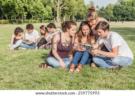 Friends using mobile devices in the park