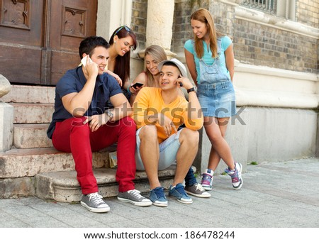 Friends using smart phones outdoors - stock photo