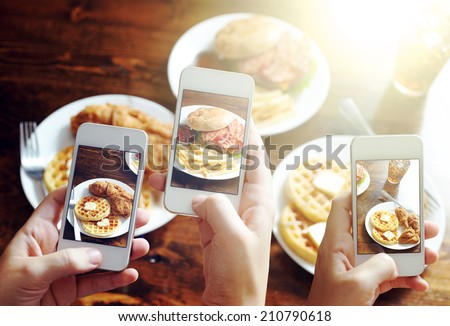 friends using smartphones to take photos of food with instagram style filter - stock photo