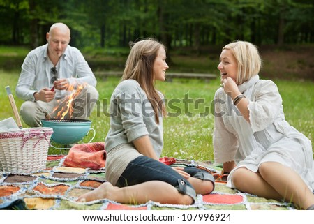 Friends visiting and preparing a barbecue for outdoor picnic - stock photo