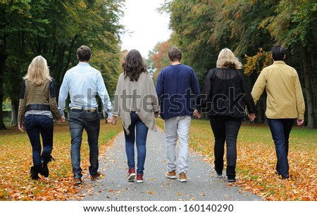 Friends walking in forest during autumn - stock photo