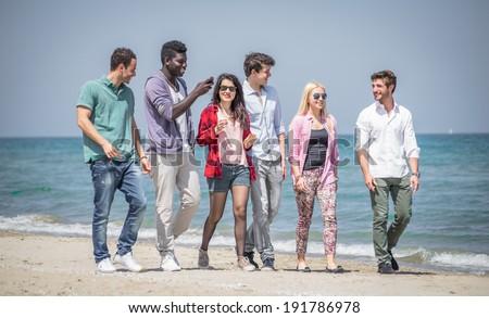 friends walking on the beach - stock photo
