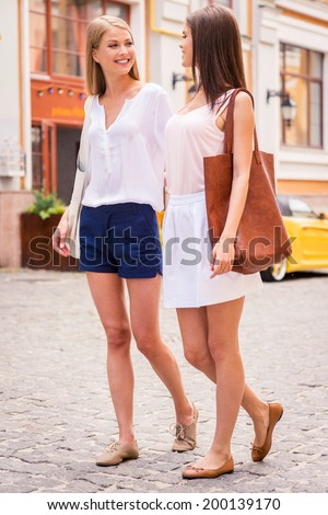 Friends walking together. Two beautiful young women walking along the street together and smiling - stock photo