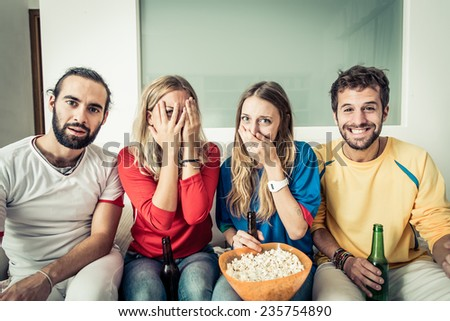 friends watching horror movie at television. different reaction on their faces - stock photo