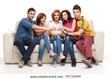 friends watching movie eating popcorn on couch - stock photo