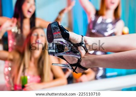 Friends watching striptease in strip club grabbing at female stripper - stock photo