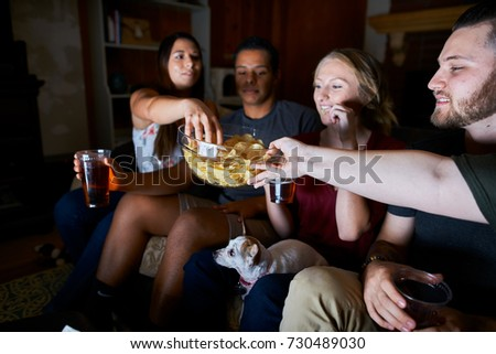 friends watching tv at night passing around snacks